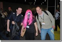 Uma moça simpática com duas figuras estranhas do lado no GeekFest